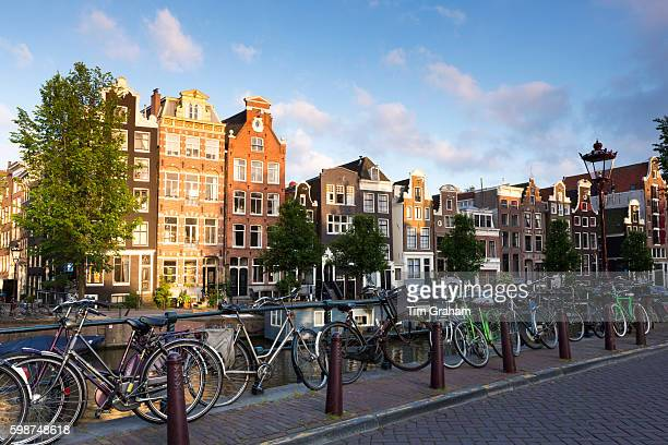 Bicycles and traditional Dutch architecture of canalside buildings in Prinsengracht Amsterdam Holland