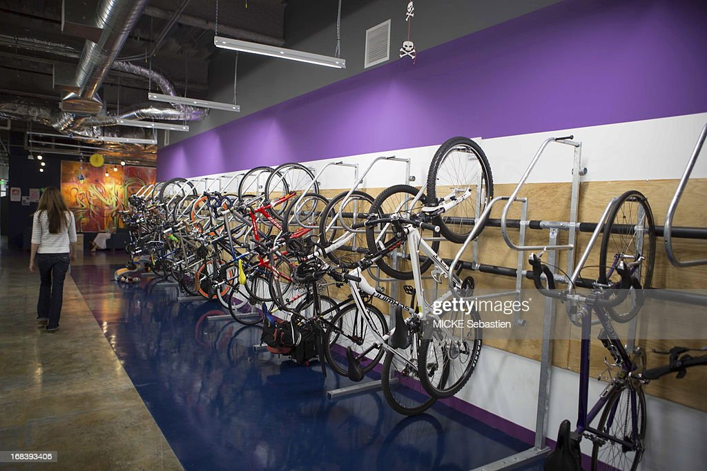 bicycles hang on the wall in one of many open work spaces at facebook menlo park office