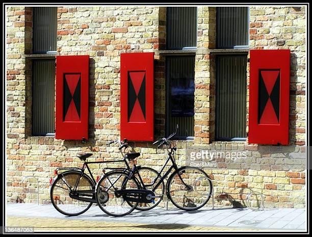 Bicycles lying against bricks wall