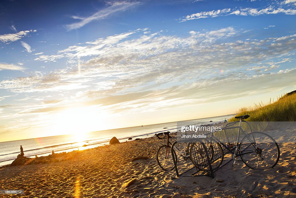 Bicycles parked on beach at sunset : Stock Photo