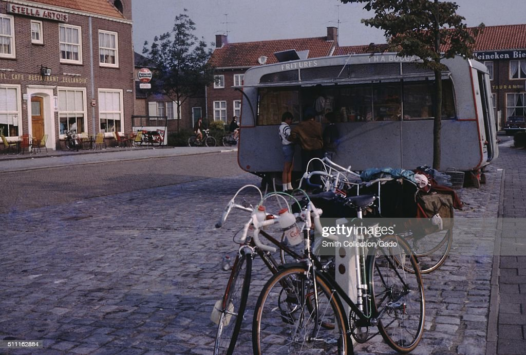 Bicycles parked outside a french fry stand in a public square with a cafe and a Stella Artois beer advertisement Holland 1960