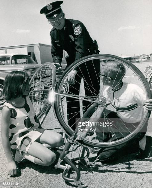 Bicycles Prizes to Be Given Cheryl Simon and Scott Barton examine a bicycle as Lt Joseph Jenkins Aurora Police Department watches They are getting...