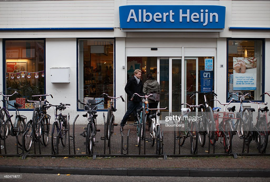 Bicycles sit in a rack outside an Albert Heijn supermarket, operated by Koninklijke Ahold NV, as customers enter in Utrecht, Netherlands, on Friday, Nov. 29, 2013. European government bonds were little changed as investors showed a muted reaction to Standard & Poor's decision to raise its outlook on Spain's debt and strip the Netherlands of its top credit rating. Photographer: Jasper Juinen/Bloomberg via Getty Images