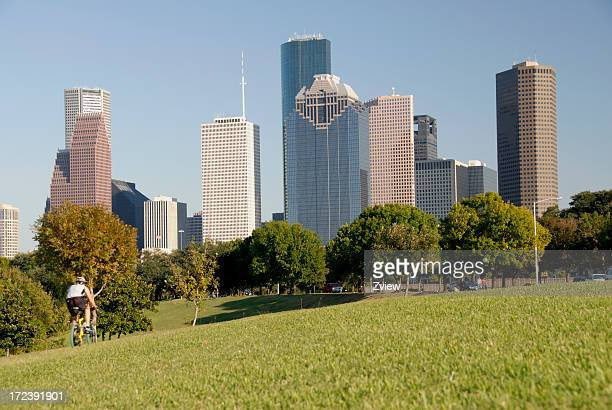 Bicycling Through A City Park -  Skyline In Background