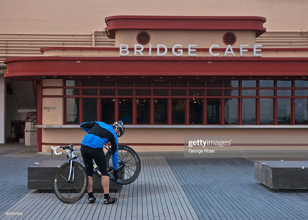 A bicyclist adjusts a tire in front of the Bridge Cafe at the Golden Gate Bridge on February 13, 2013, in San Francisco, California. Some 13.6 million international travelers visit the State each year generating nearly $100 billion in revenue and creating approximately 900,000 jobs in the arts, entertainment, recreation, food service and accomodations sectors.