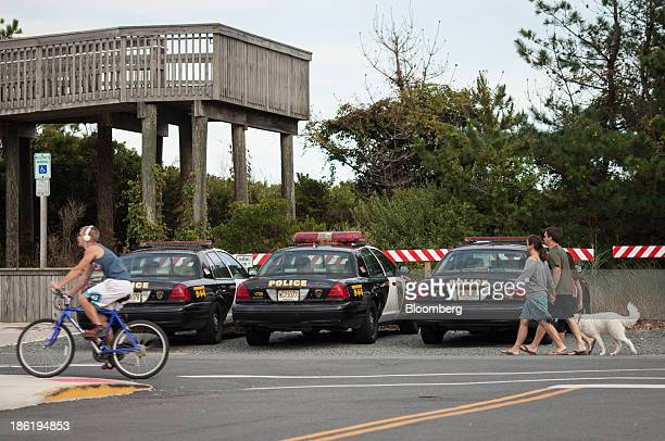 A bicyclist and pedestrians with a dog pass parked police cruisers on Long Beach Island in Long Beach Township New Jersey US on Thursday Sept 26 2013...