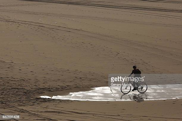 A bicyclist comes to the end of a bike trail that's covered in wet sand at Dockweiler State Beach in Playa del Rey on January 23 2017