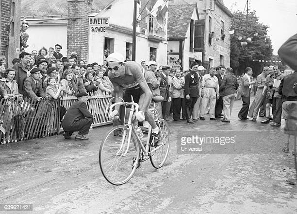 Bicyclist Fausto Coppi races past a crowd of spectators as he enters the RennesAngers stage of the 1951 Tour de France | Location Between Rennes and...