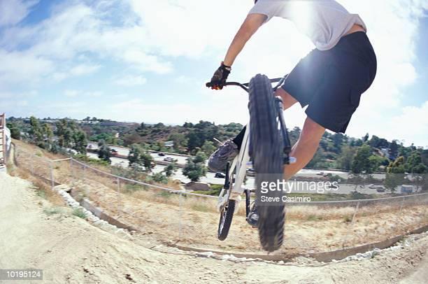 BMX bicyclist in midair, rear view