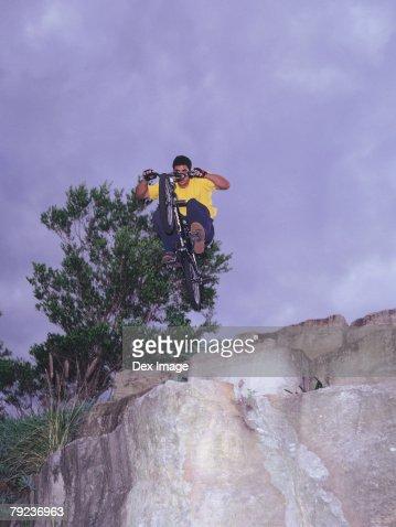BMX bicyclist in midair, underneath view : Stock Photo