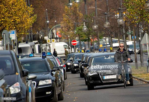 A bicyclist leads a convoy of ministerial cars arriving for coaltition talks in Berlin Germany on October 23 2013 AFP PHOTO / ODD ANDERSEN