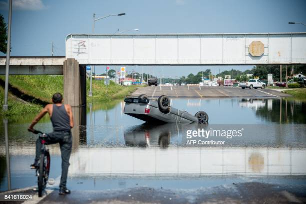 TOPSHOT A bicyclist looks at a truck flipped into floodwater in Port Arthur Texas on September 1 2017 Houston was limping back to life on Friday one...