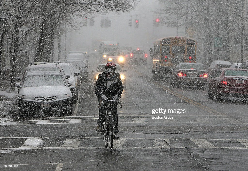 A bicyclist makes his way down Dorchester Ave in South Boston as more snow falls on February 27 2014