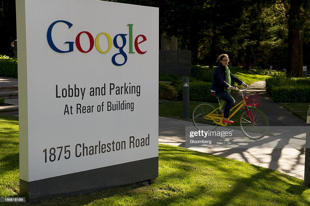 A bicyclist passes in front of Google Inc. signage displayed outside of the company's headquarters in Mountain View, California, U.S., on Tuesday, April 16, 2013. Google Inc. is expected to release earnings data on April 18. Photographer: David Paul Morris/Bloomberg via Getty Images