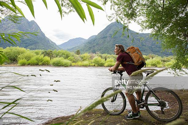Bicyclist pauses at edge of river, looks to hills