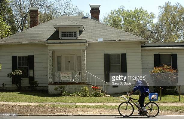 A bicyclist pauses to read a sign hanging on 610 North Buchanan April 11 2006 in Durham North Carolina The house was rented by Duke University...