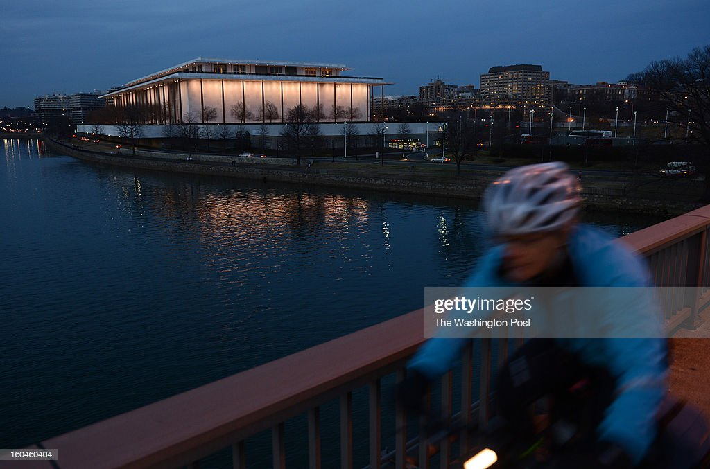 A bicyclist pedals across the Theodore Roosevelt Memorial Bridge as the John F. Kennedy Center for the Performing Arts is seen on Tuesday January 29, 2013 in Washington, DC. The Kennedy Center is planning a large expansion.