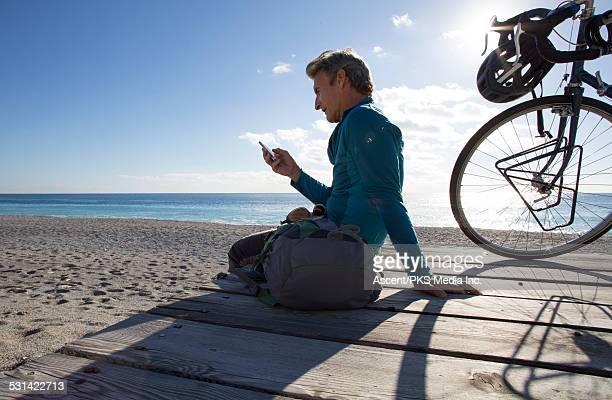 Bicyclist relaxes on beach wharf, sends text