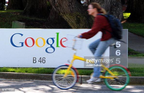 A bicyclist rides by a sign at the Google headquarters March 10 2010 in Mountain View California Google announced today that they are adding bicycle...