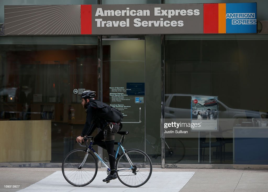 A bicyclist rides by an American Express Travel Services office on January 11, 2013 in San Francisco, California. American Express Co. is planning to cut 5,400 jobs, or 8.5% of its workforce. Most of the cuts will fall on its struggling travel division that has been unable to keep up with low cost internet travel sites.