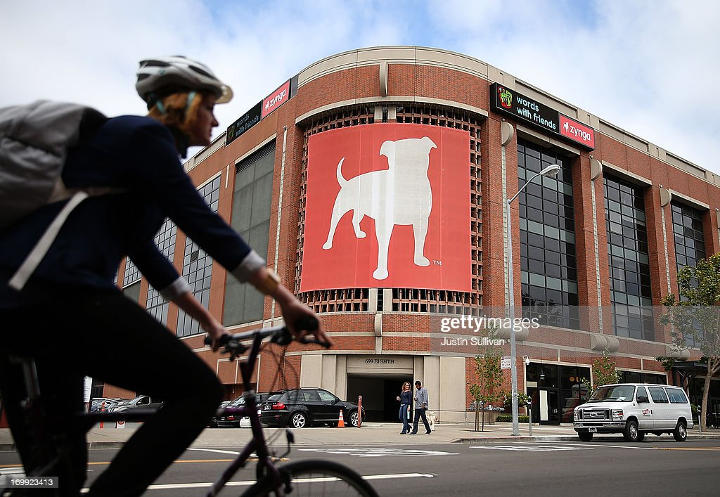 A bicyclist rides by the Zynga headquarters on June 4, 2013 in San Francisco, California. Mobie game maker Zynga announced on Monday that they will cut 18 percent of their workforce and shut down offices in Los Angeles, Dallas and New York. The layoffs will save the struggling company an estimated $70 to $80 million.