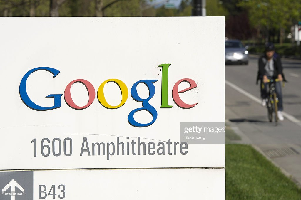 A bicyclist rides next to Google Inc. signage displayed outside of the company's headquarters in Mountain View, California, U.S., on Tuesday, April 16, 2013. Google Inc. is expected to release earnings data on April 18. Photographer: David Paul Morris/Bloomberg via Getty Images