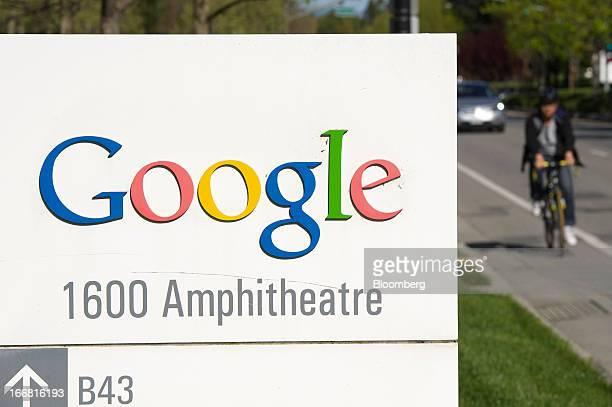 A bicyclist rides next to Google Inc signage displayed outside of the company's headquarters in Mountain View California US on Tuesday April 16 2013...