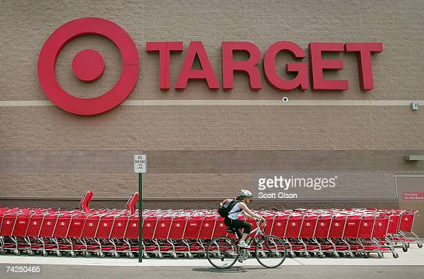 A bicyclist rides past a row of shopping carts outside a Target store on May 23 2007 in Chicago Illinois Today Target reported an 18 per cent...