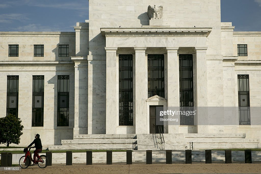 A bicyclist rides past the Marriner S. Eccles Federal Reserve building in Washington, D.C., U.S., on Tuesday, Oct. 23, 2012. Federal Reserve Chairman Ben S. Bernanke, who is seeking to spur the economy with a third round of so-called quantitative easing, has said his stimulus works by lowering borrowing costs and encouraging investors to seek higher-yielding assets. Photographer: Andrew Harrer/Bloomberg via Getty Images
