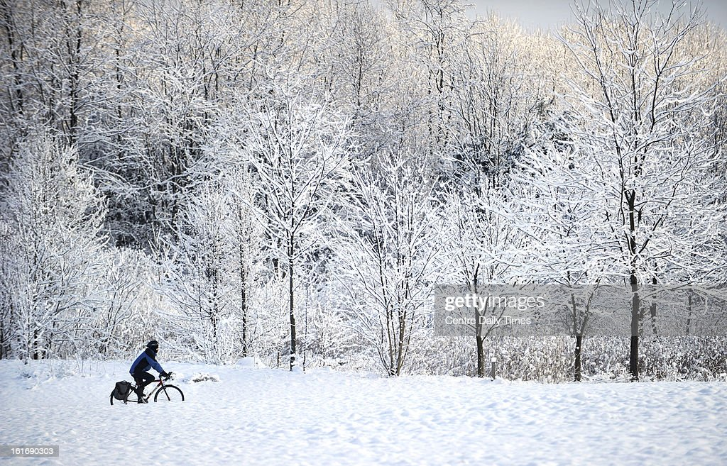 A bicyclist rides through a snow-covered Tom Tudek Memorial Park, in State College, Pennsylvania, Thursday, February 14, 2013.