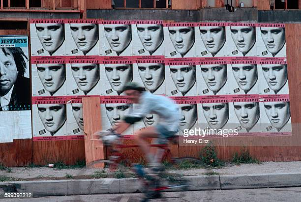 A bicyclist speeds past a wall covered with posters for the movie This Is Elvis featuring the face of Elvis Presley | Location Toluca Lake Los...