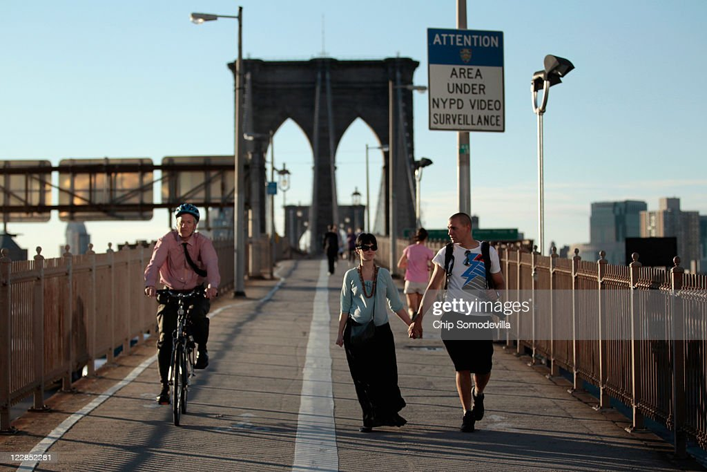 Bicyclists and pedestrians walk across the Brooklyn Bridge into Manhattan August 29, 2011 in New York City. One day after Hurricane Irene hit New York and New England, the mass transit system, including subways and buses, began moving again in a limited capacity in time for Monday's rush hour.