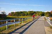 Bicyclists on path through salt marsh, Falmouth