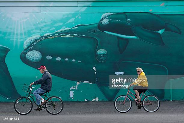Bicyclists ride past a mural on Long Beach Island in Beach Haven New Jersey US on Thursday Sept 26 2013 At the height of tourist season 150000 people...