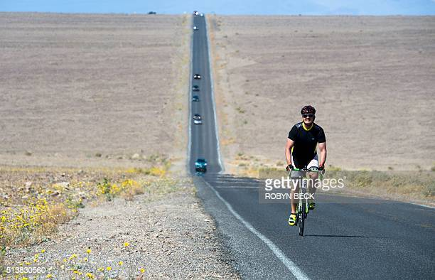 A bicyclists rides along a wildflowerlined highway through Death Valley National Park in Death Valley California March 4 2016 Unusally heavy rainfall...