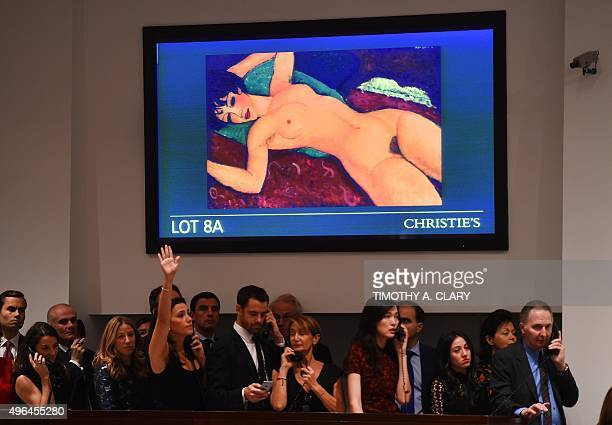 Bid takers stand in front of a video screen with Amedeo Modigliani's 'Nu couche' during the 'Artist Muse A Curated Evening Sale' November 9 2015 at...