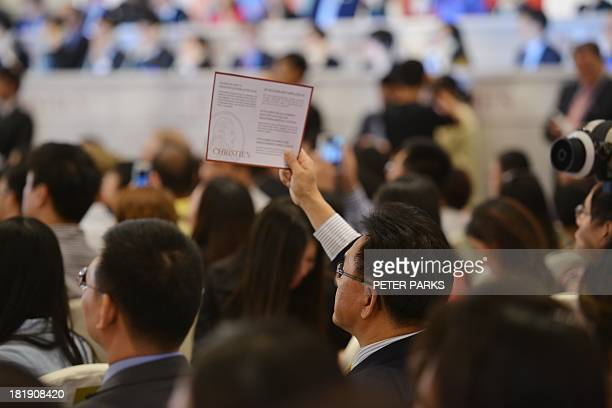 A bidder holds up his card at a Christie's auction in Shanghai on September 26 2013 Christie's kicked off its first independent auction in mainland...