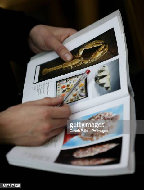 A bidder looks at his sale catalogue during an Evolution sale at Summers Place Auctions in West Sussex which featured a 17 metre long specimen of a...