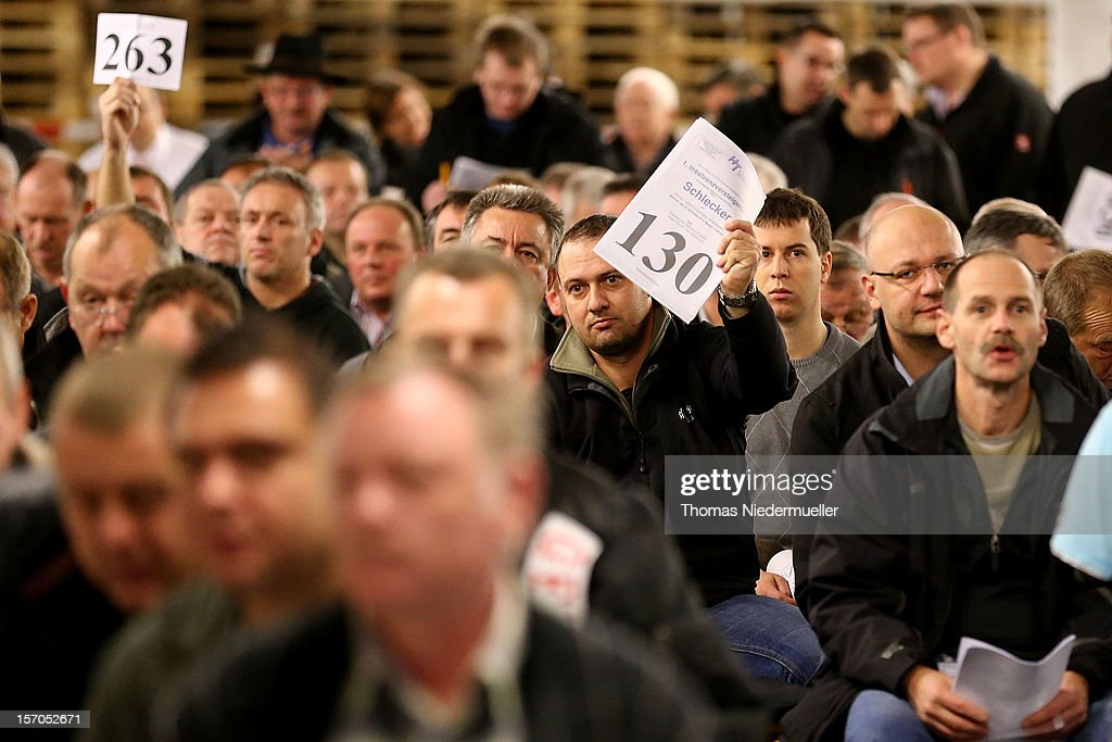 Bidders hold up their numbers during a final auction at Schlecker headquarters on November 28 2012 in Ehingen Germany Schlecker which operated...