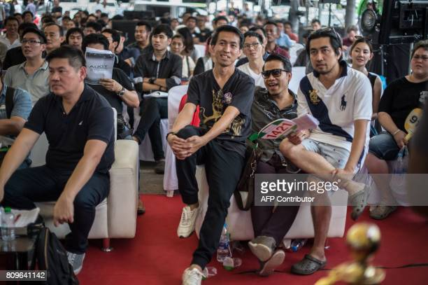 Bidders look at the screen during a luxury car auction by the Thai customs department in Bangkok on July 6 2017 Thai customs officials sold off...