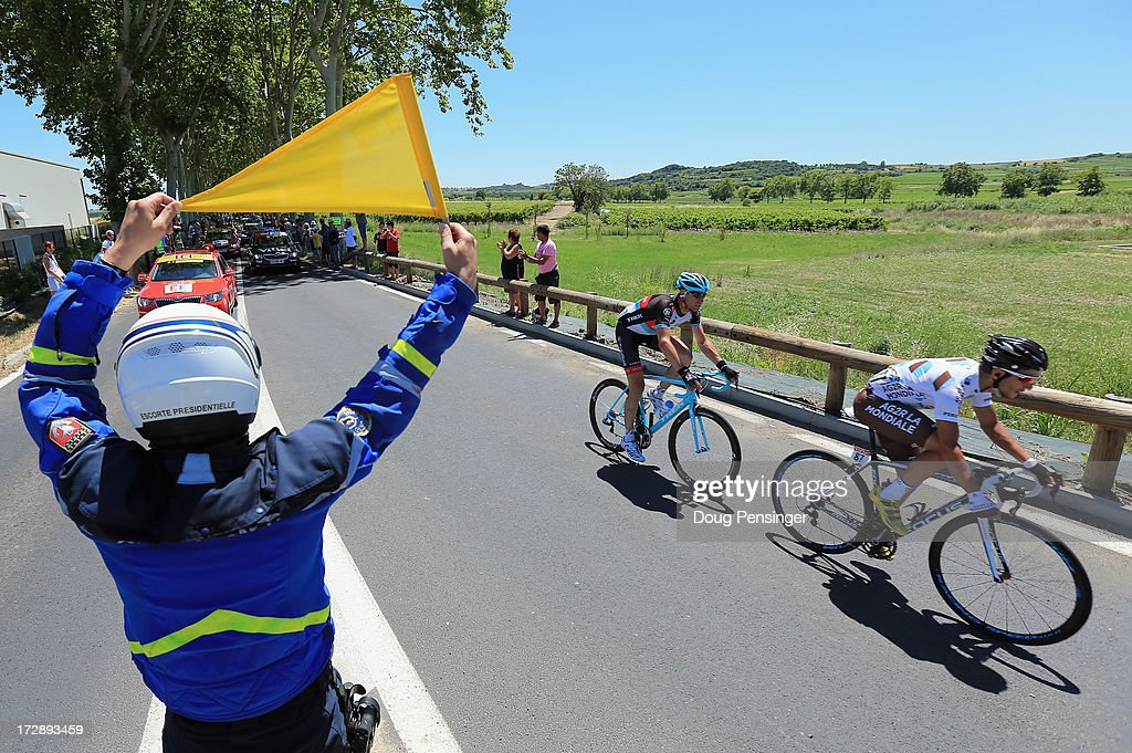 Biel Kadri (R) of France riding for AG2R-La Mondiale leads <a gi-track='captionPersonalityLinkClicked' href=/galleries/search?phrase=Jens+Voigt&family=editorial&specificpeople=224836 ng-click='$event.stopPropagation()'>Jens Voigt</a> (C) of Germany riding for RadioShack Leopard in the breakaway as a Gendarme (L) shows a caution flag for an obstacle during stage seven of the 2013 Tour de France, a 205.5KM road stage from Montpellier to Albi, on July 5, 2013 in Albi, France.