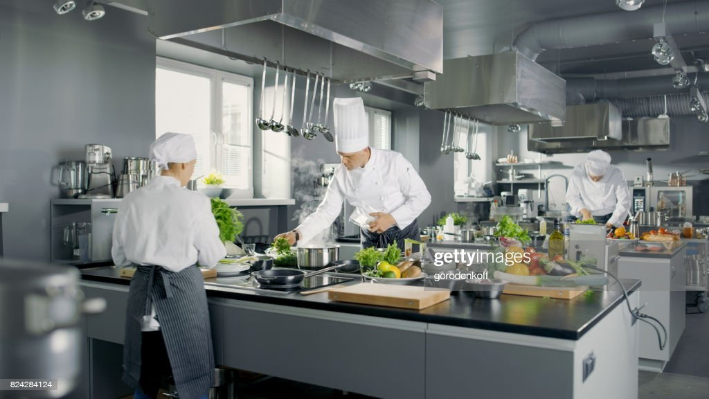 Big And Glamorous Restaurant Busy Kitchen, Chefs And Cooks Working On Their  Dishes. :