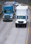 Big blue rig with bulk semi trailer and middle size white local semi truck with box trailer making deliveries and drive on one way turning overpass road intersection in front of another car traffic