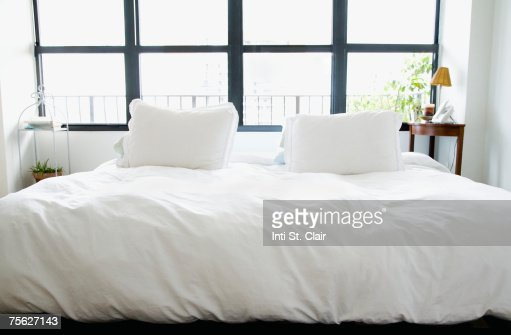 Big bed with white bedclothes next to window : Stock Photo