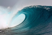 Big blue surfing wave breaking over coral reef in the Mentawai Island, Sumatra, Indonesia