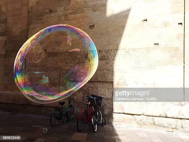 Big Bubble In Mid-Air By Bicycle Parked Against Wall