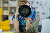 A female Caucasian photographer is indoors in a design studio. She is wearing casual clothing and a stylish shawl. She is holding up a highly customized camera and pointing it forward.