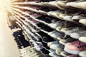 Big collection of different sport shoes. The shop window is filled with a large number of sports shoes of different colors. Men's women's shoes unisex