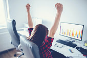 Portrait of happy young successful businesswoman celebrate something with arms up. Happy woman sit at office and look at Computer/ laptop. Positive emotion. Big deal, promotion, lottery win or discoun