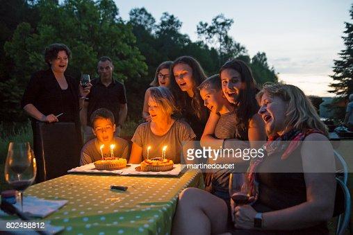 Big dinner: grandmother celebrating birthday outdoors at dusk. : Stock Photo